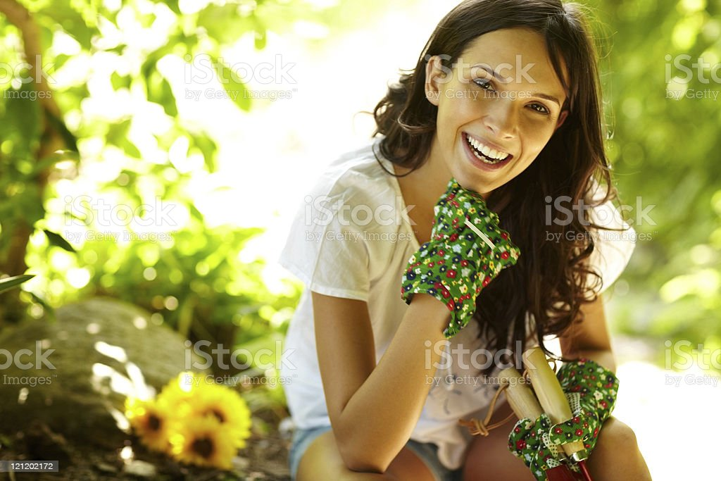 Pretty female gardner relaxing outdoors holding gardening tools royalty-free stock photo