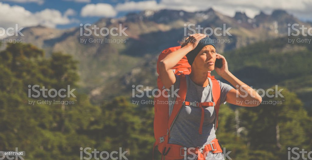 Pretty, female hiker in high mountains , calling for help stock photo