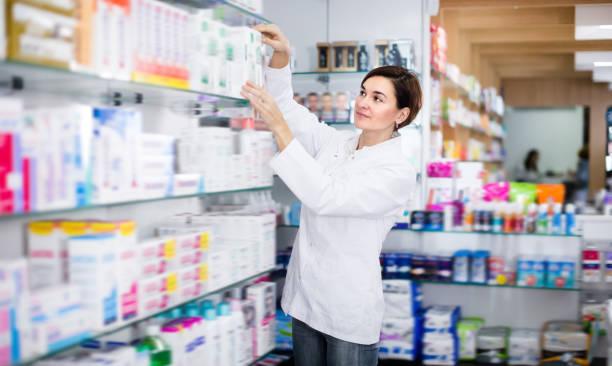 pretty female pharmacist offering products - farmácia imagens e fotografias de stock