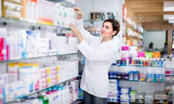 Pretty Female Pharmacist Offering Products - Fotografias de stock e mais imagens de Adulto
