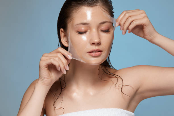 pretty female taking off purifying mask with her eyes closed pretty female taking off purifying mask with her eyes closed, girl with wet hair removing moisturizer, fresh and clean skin peel plant part stock pictures, royalty-free photos & images