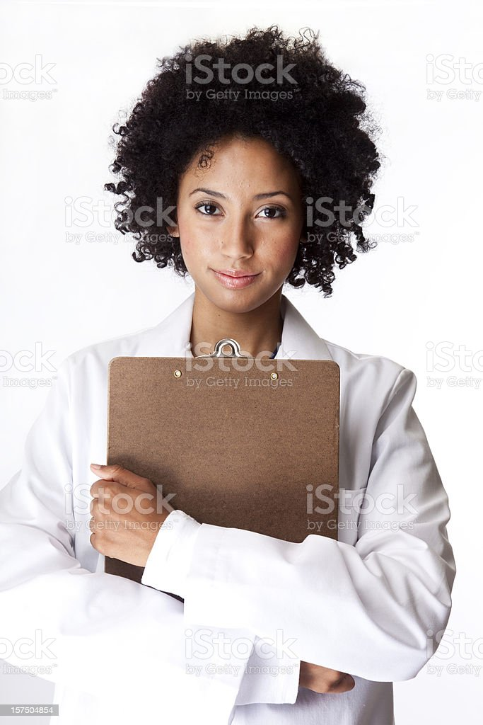 pretty female technician in white lab coat carrying clipboard royalty-free stock photo