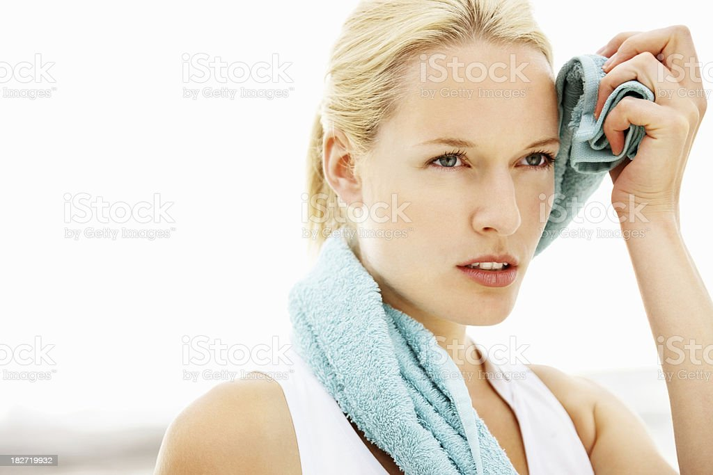Pretty female wiping her face after workout stock photo