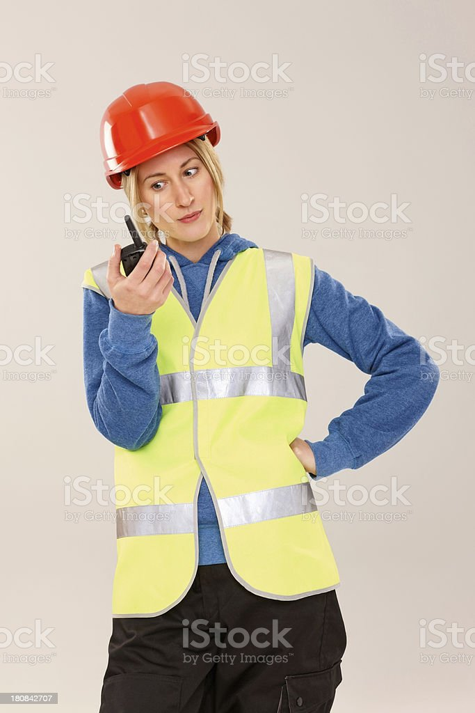 Pretty female worker looking at walkie talkie in her hand royalty-free stock photo