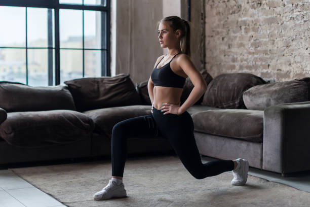Pretty fit woman doing frontal lunges or squat exercise indoors in a flat stock photo