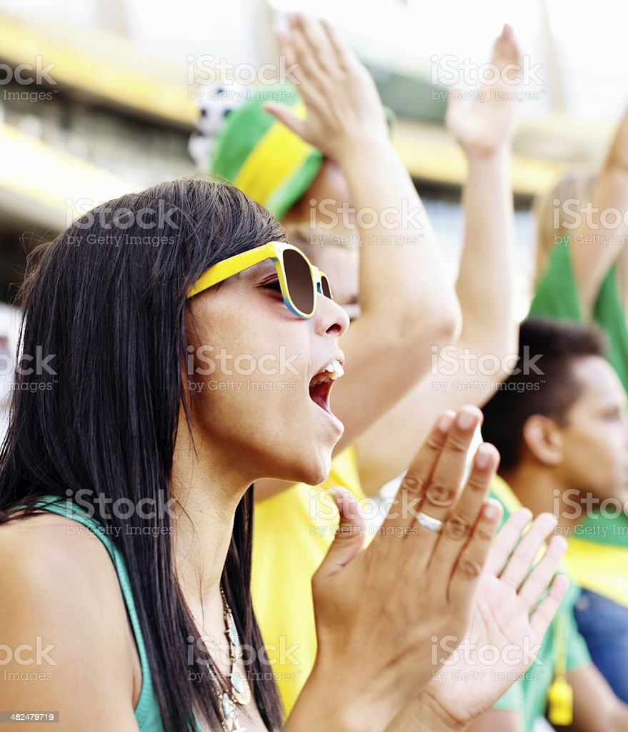 Pretty football fan cheering and clapping at soccer match stock photo