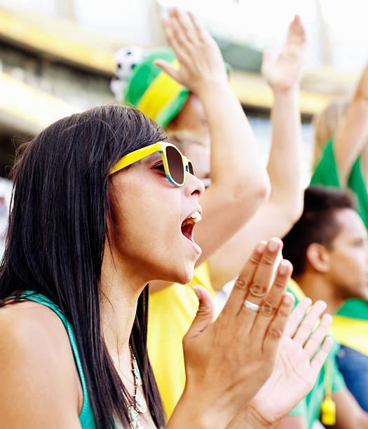 schöne fußball-fan jubeln und klatschen im fußballspiel - spielerfrauen stock-fotos und bilder