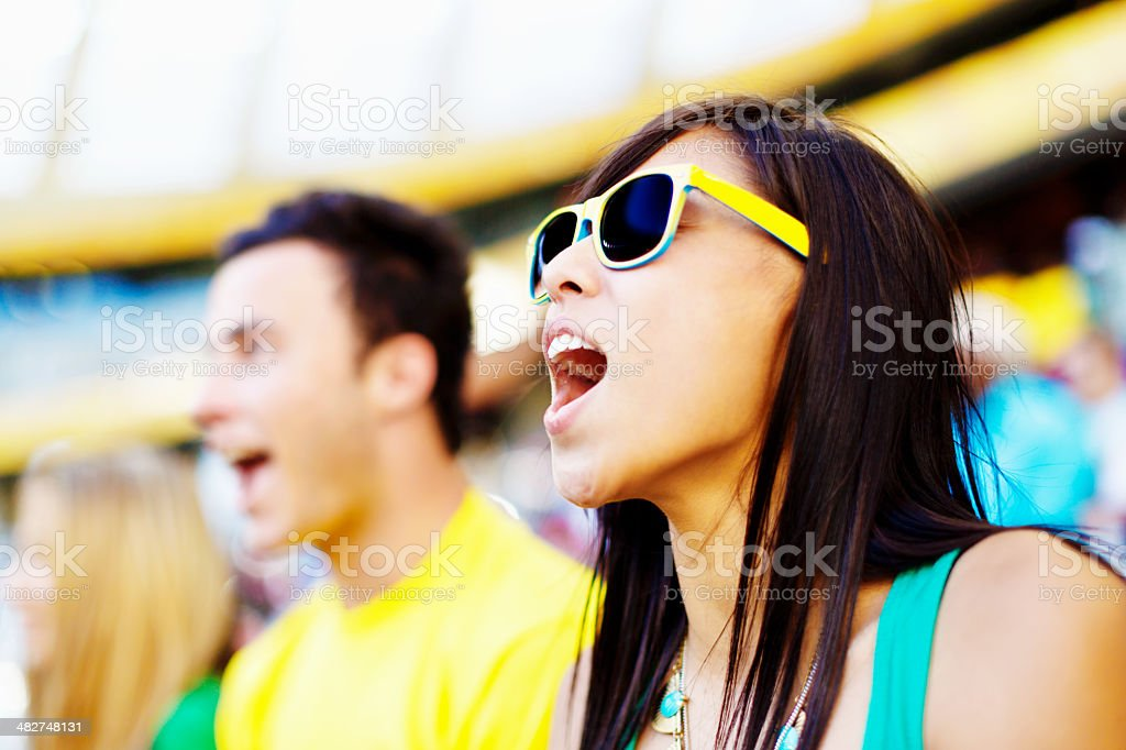 Pretty football fan cheers her team at match stock photo