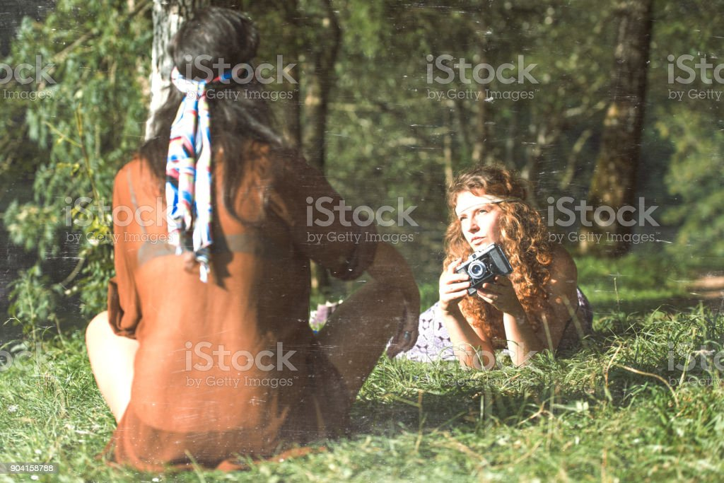 Pretty free hippie girls on the grass taking photos with an old - Vintage effect photo stock photo