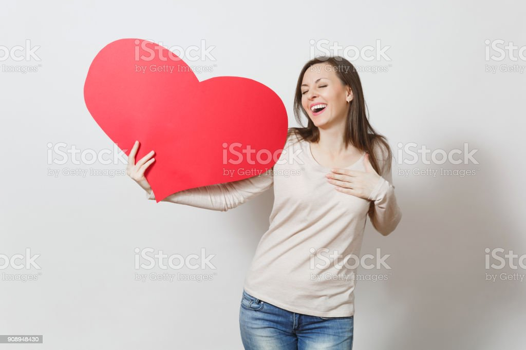 Pretty fun young smiling woman holding big red heart in hands isolated on white background. Copy space for advertisement. With place for text. St. Valentine's Day or International Women's Day concept. stock photo