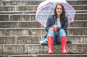 istock Pretty girl awaits her date sitting on stone stairs protecting herself from rain by an umbrella. 1240303446