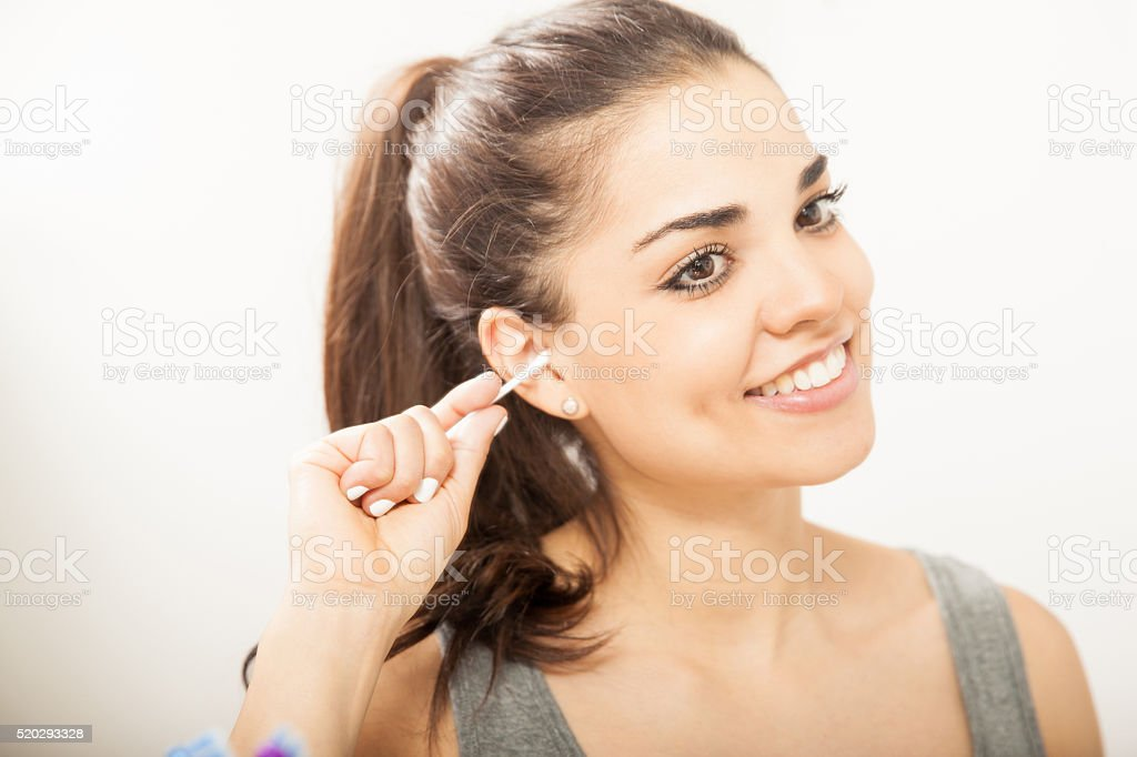 Pretty girl cleaning her ears in a bathroom stock photo