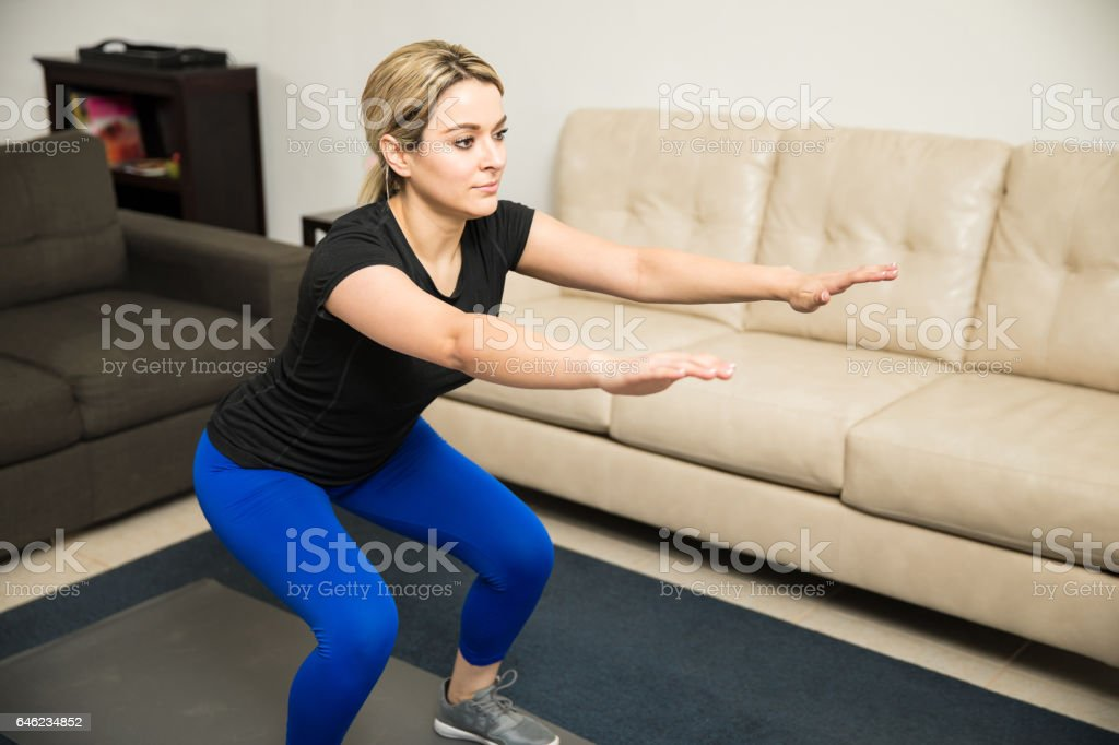 Pretty girl doing some squats at home stock photo