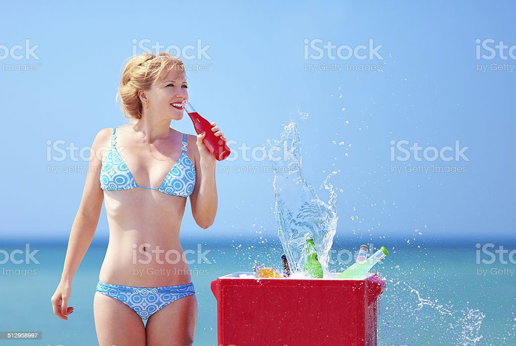 pretty girl drinks fresh beverages on beach stock photo