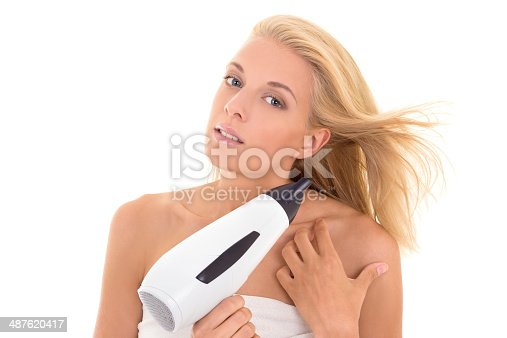 639833996istockphoto pretty girl drying her hair with hairdryer 487620417