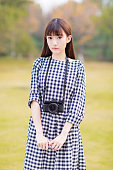 chinese girl in the park alone , using SLR camera beautiful scenery