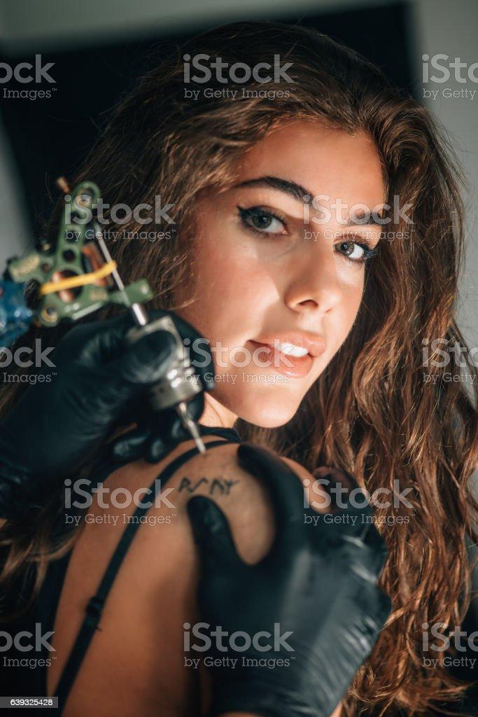 Pretty girl getting a tattoo stock photo