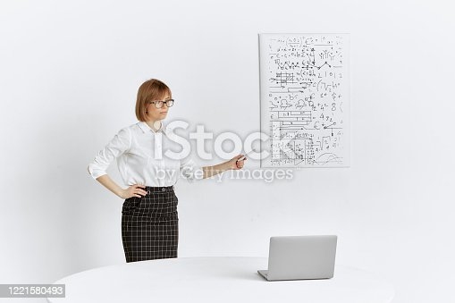 istock A pretty girl gives a presentation to colleagues remotely at an online conference on a laptop while staying at home. 1221580493