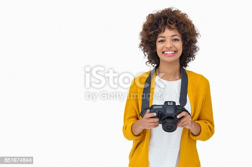 Pretty girl holding a camera on white background