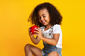 Healthy nutrition. Pretty girl holding red apple over yellow studio background