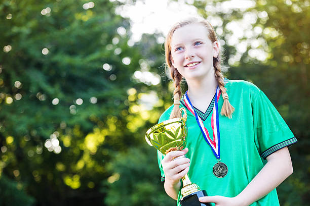 Pretty girl holding up the winning soccer trophy stock photo