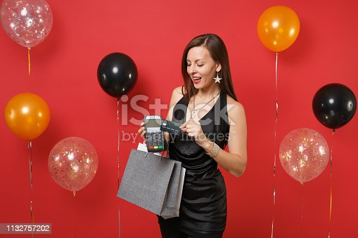 istock Pretty girl holding wireless modern bank payment terminal credit card packages bags with purchases after shopping on red background air balloons. Happy New Year, birthday mockup holiday party concept. 1132757202