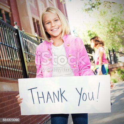 istock Pretty girl holds 'thank you' sign at school 534323090