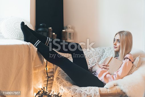 Young woman chilling at home in a comfortable round armchair near the window. Girl relaxing, reading and dreaming book in the loft living room. Imagining the book extraordinary world.