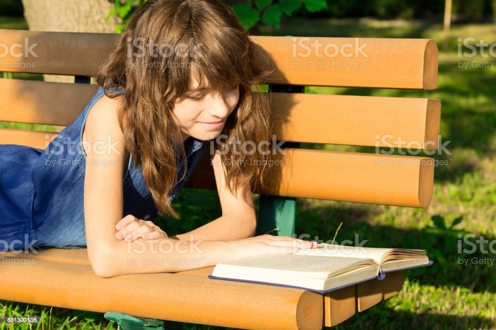 Pretty girl in a jean dress is lying on a bench in the park, reading a book and smiling stock photo