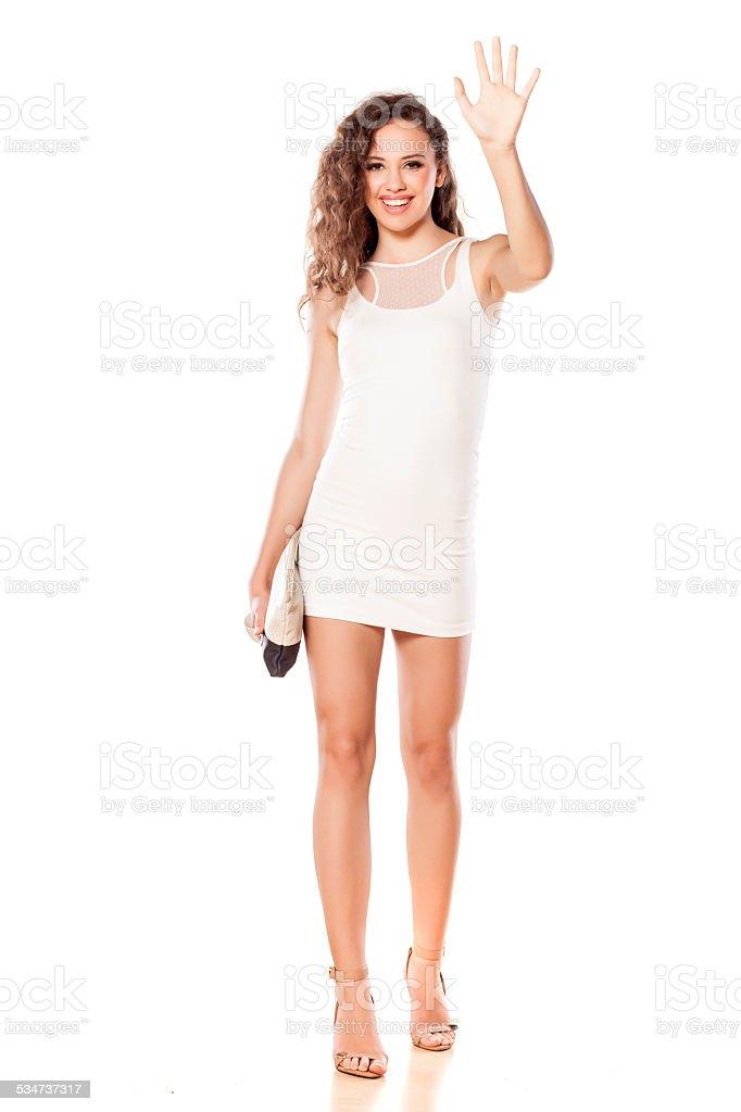 Pretty girl in a short white dress waving hand stock photo