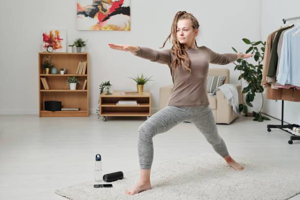 Hübsche Mädchen in Activewear Strecken Beine und Arme beim Training auf Teppich – Foto