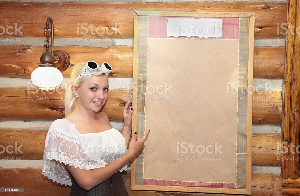 pretty girl in blouse and goggles shows sign board stock photo