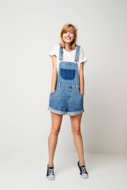 Pretty girl in denim posing Pretty girl in denim posing to camera, portrait bib overalls stock pictures, royalty-free photos & images