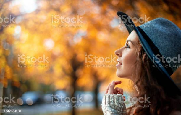 Photo of Pretty girl in hat standing on colorful autumn leaves background