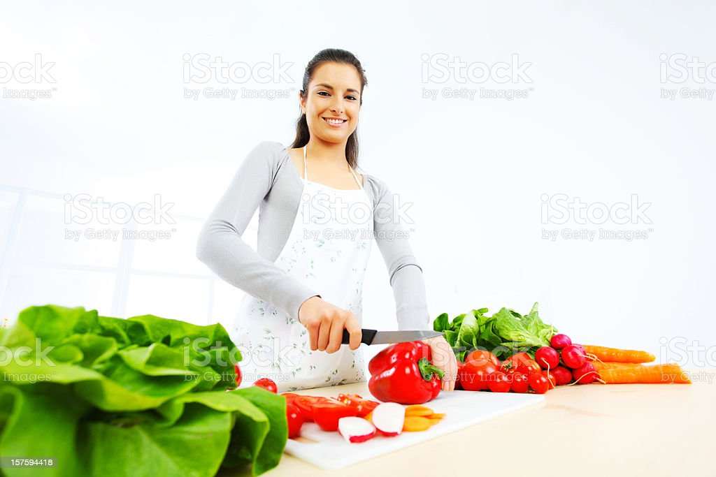 Pretty girl in her kitchen cutting vegetable ingredients. royalty-free stock photo
