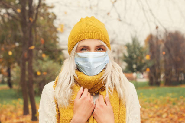 Pretty girl in medical face mask walking outdoors Pretty girl in medical face mask walking outdoors allergy stock pictures, royalty-free photos & images