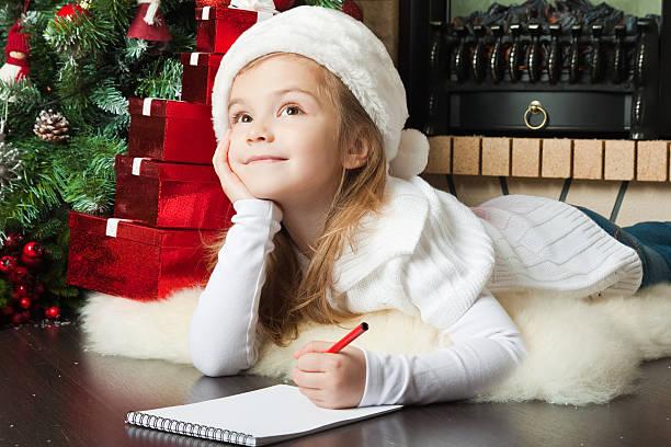 hübsches mädchen in weihnachtsmütze schreibt buchstabe - weihnachten 7 jährige stock-fotos und bilder