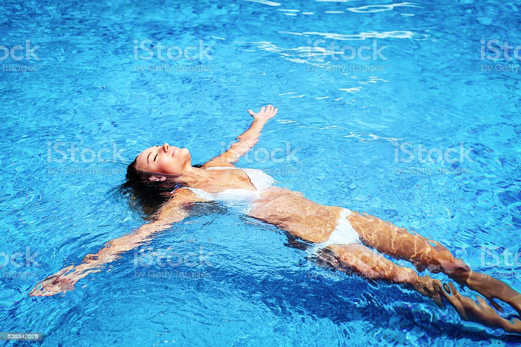 Pretty girl in swimming pool stock photo