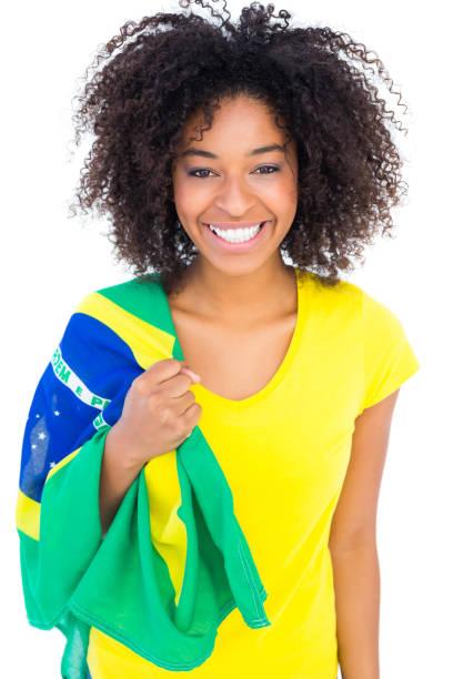 Menina bonita no tshirt amarelo segurando a bandeira brasileira, sorrindo para a câmera - foto de acervo