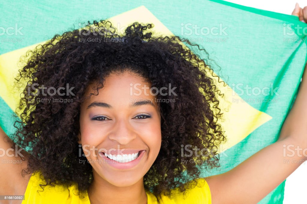 Pretty girl in yellow tshirt holding brazilian flag smiling at camera stock photo