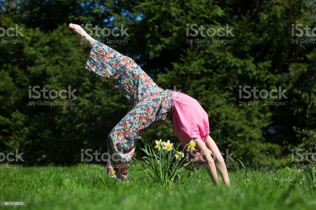 A pretty girl is exercising on the lawn – zdjęcie