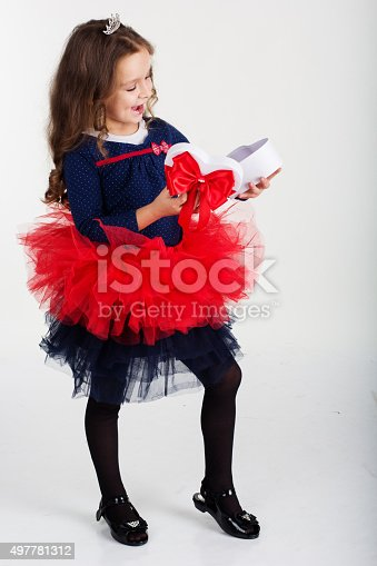 1061876006istockphoto Pretty girl is holding gift box with red ribbon 497781312