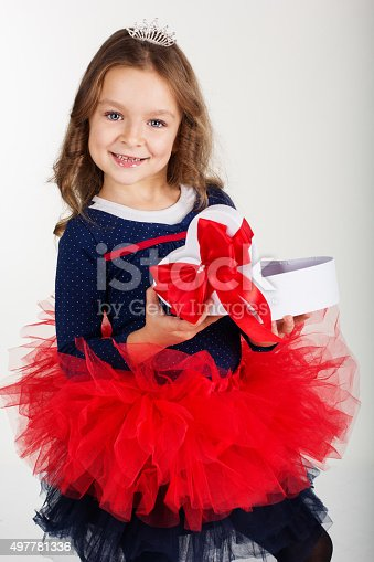 1061876006istockphoto Pretty girl is holding gift box with red ribbon 497781336