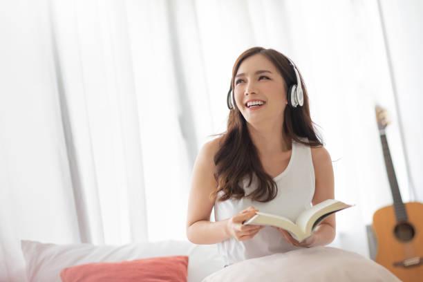 La chica bonita se ríe y sostiene un libro en la habitación blanca. - foto de stock