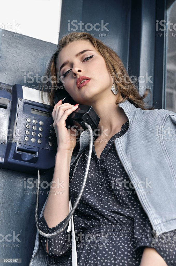 Pretty girl languidly talking on a pay phone foto de stock royalty-free