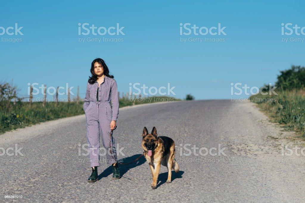 Ein hübsches Mädchen führt einen Hund neben ihr auf der Straße - Lizenzfrei Abwarten Stock-Foto