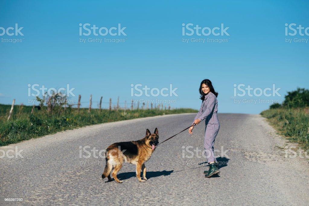 A pretty girl leads a dog next to her on the road zbiór zdjęć royalty-free