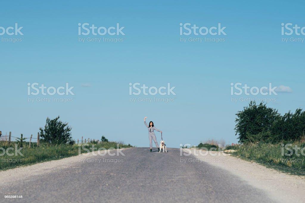 一個漂亮的女孩在路上領著一條狗在她身旁。 - 免版稅一個人圖庫照片