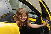 Pretty girl open door of yellow sport car and looking at camera. She is seven years old and have long haird down.