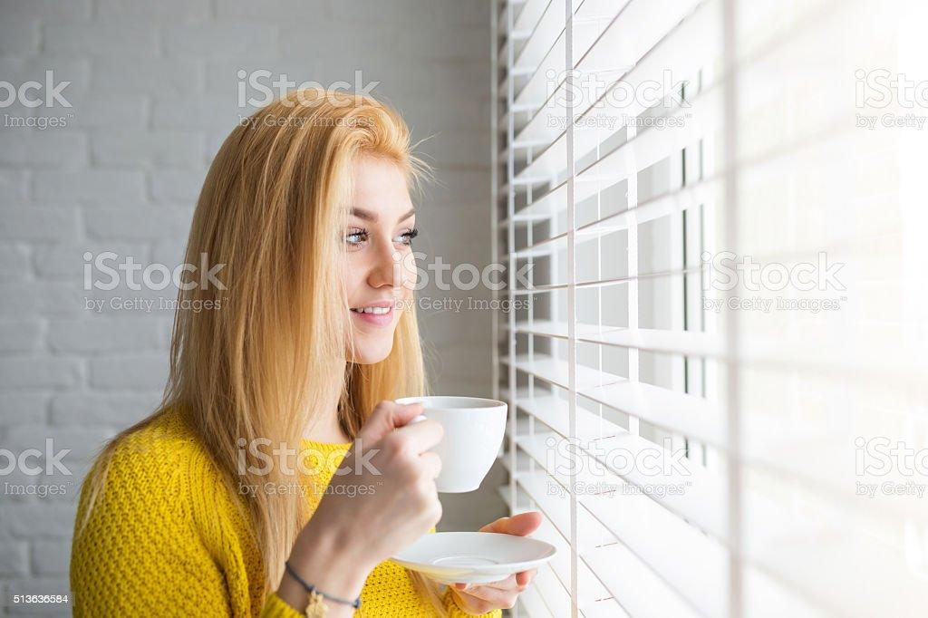 Ładna dziewczyna patrzy na zewnątrz okno – zdjęcie